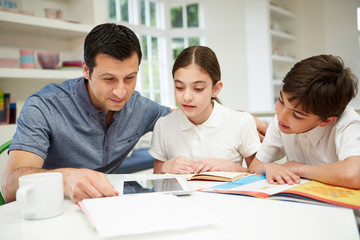 Father Helping Children With Homework Using Digital Tablet