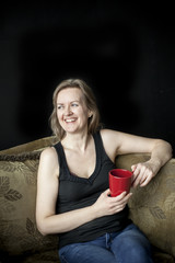 Laughing Blonde Woman with Red Coffee Cup on Black Background