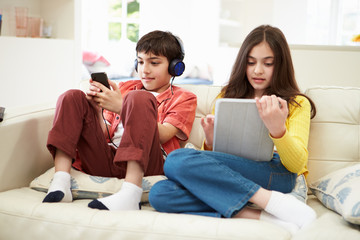 Children Playing With Digital Tablet And MP3 Player