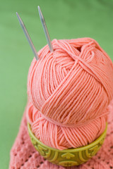 One ball of pink yarn and knitting needles on plate
