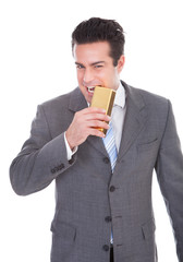 Businessman Biting Gold Bar