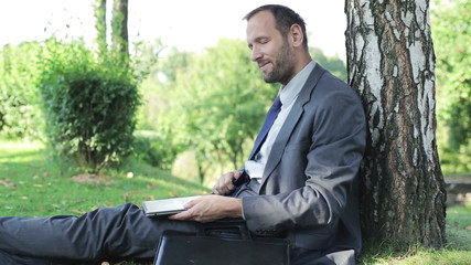 businessman finishing work on his laptop  and smiling to the cam
