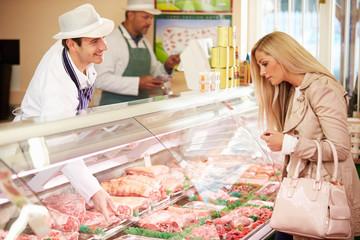 Butcher Serving Customer In Shop
