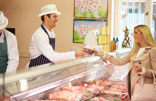 Butcher Serving Customer In Shop