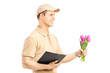 Delivery person holding a clipboard and bunch of flowers