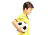 Sad kid in sportswear posing with a soccer ball