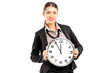 Smiling female standing and holding on a wall clock