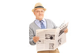 Senior gentleman holding newspaper and leaning against a wall