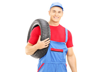 Male mechanic holding a vehicle tires and looking at camera