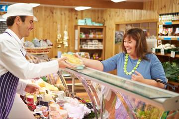 Male Sales Assistant Serving Customer In Delicatessen