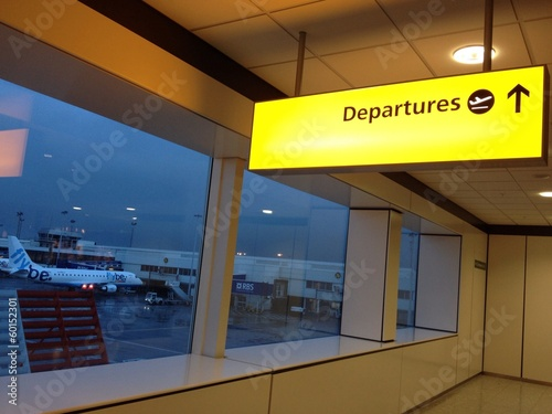 Departure sign in an airport with plane in the background