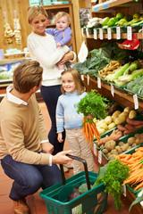 Family Choosing Fresh Vegetables In Farm Shop