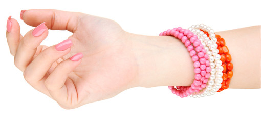 Female hand with pink manicure and bright bracelets, isolated