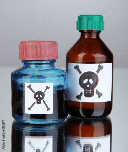 Deadly poison in bottles on grey background