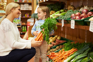 Mother And Daughter Choosing Fresh Vegetables In Farm Shop
