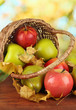 Beautiful ripe apples and pears with yellow leaves in basket