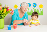 loving grandma teaching grandson drawing at home