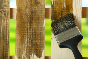 Applying protective varnish to wooden fence,