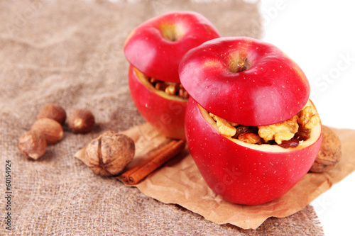 Stuffed apples with nuts and cinnamon on sackcloth close up