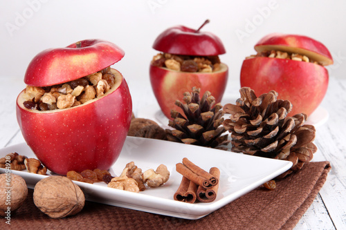 Stuffed apples with nuts and cinnamon on plate on table close