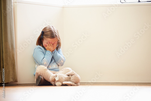 Unhappy Child Sitting On Floor In Corner At Home - 60155364