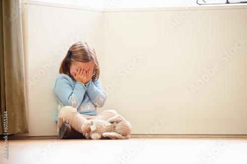 Leinwanddruck Bild Unhappy Child Sitting On Floor In Corner At Home