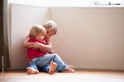 Unhappy Children Sitting On Floor In Corner At Home