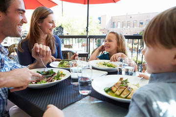Family Enjoying Meal At Outdoor Restaurant
