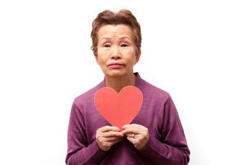 高齢の女性と赤いハートマーク