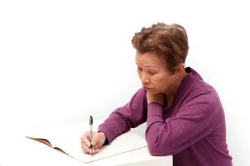 文書をノートに書いている高齢の女性