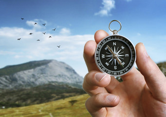 Man holding a compass over a landscape view