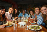 Fototapety Group Of Friends Enjoying Meal In Restaurant