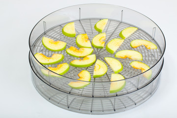 sliced green apple in Food dryer on white background