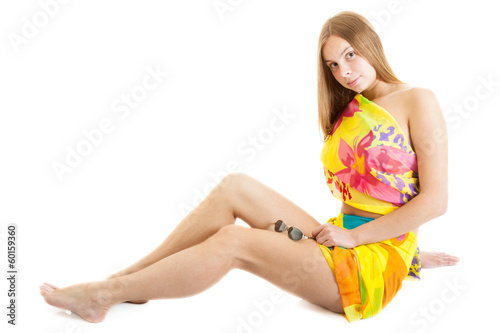 sensual young blonde woman wearing a bright pareo seats