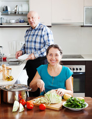 mature married couple cooking  together