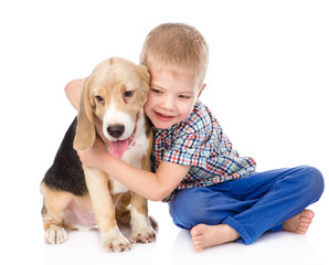 little boy hugging beagle puppy. isolated on white background