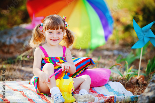 Adorable toddler girl playing outdoors in green summer park