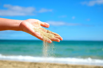 Sand falling from the woman hand.Travel time, relax