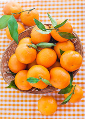 Fresh tangerines with leaves in a  basket
