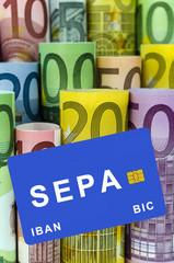 Euro-Geldscheine und blaue Bankkarte: SEPA