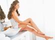 Happy woman sitting in bathroom and checking leg skin softness