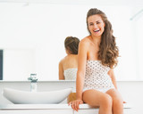 Portrait of smiling young woman sitting in bathroom