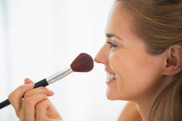 Happy young woman using makeup brush