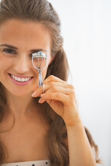 Happy young woman using eyelash curler