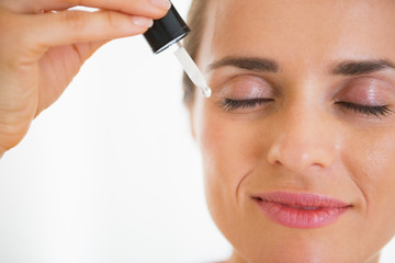 Happy young woman applying cosmetic serum