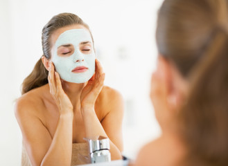 Young woman applying facial mask in bathroom