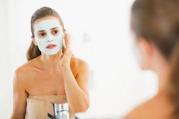 Young woman applying facial mask in bathroom