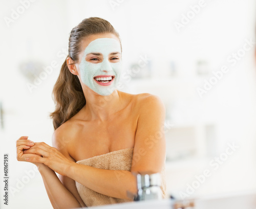 Portrait of smiling young woman with cosmetic mask on face