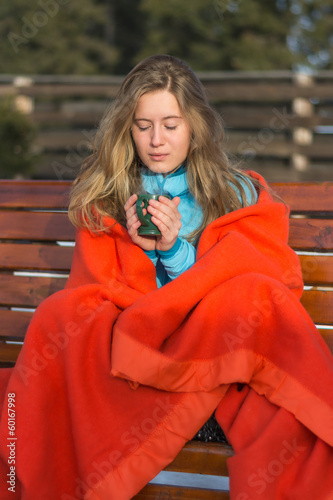 young women in a blanket blows in her hot coffe on a chilly wint
