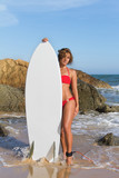 Beautiful sexy young woman surfer girl in bikini with surfboard